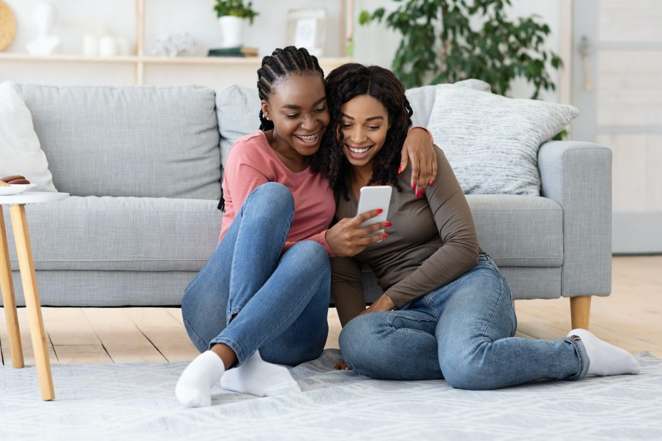 Two cheerful african american sisters checking social media on smartphone